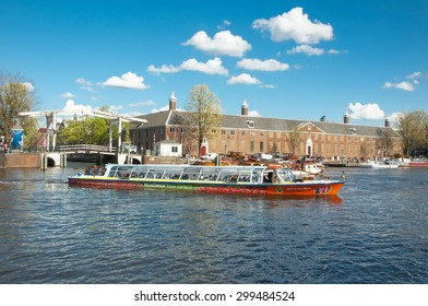 Amsterdam-April 30: Amsterdam cityscape, tourists enjoy canal cruise, Magere Brug (Skinny Bridge) and Hermitage Amsterdam are visible on the background on April 30, 2015, the Netherlands.