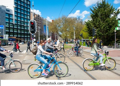 AMSTERDAM-APRIL 30: Local people on bicycles cross the road on April 30,2015, the Netherlands. There are more bicycles then people in Amsterdam.