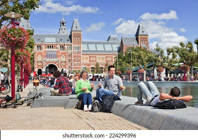 AMSTERDAM-AUG. 24, 2014. People enjoy a summer day on Museum Square. Several museums are located around the very touristy square: Rijksmuseum, Van Gogh Museum, Stedelijk Museum and Diamond Museum.