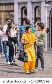 AMSTERDAM-AUG. 8, 2019. Asian tourists on Dam Square. Many popular tourist cities are seriously trying to tackle the mass tourism wave, Amsterdam is establishing itself as a forerunner among them.