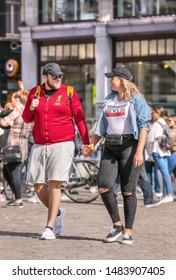 AMSTERDAM-AUG. 8, 2019. Cheerful tourists on Dam Square. Many popular tourist cities are seriously trying to tackle the mass tourism wave, Amsterdam is establishing itself as a forerunner among them.