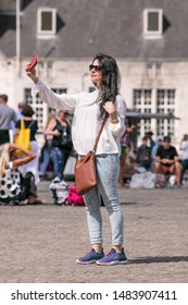 AMSTERDAM-AUG. 8, 2019. Tourist makes selfie on Dam Square. Selfies are incredible popular worldwide and often shared on social networking services such as Facebook, Twitter, Snapchat and Instagram.