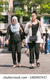 AMSTERDAM-AUGUST 8, 2019. Islamic people on a sunny Dam Square. With approximately 178 different cultural backgrounds, Amsterdam is a lively, colorful blend of people from all over the world.