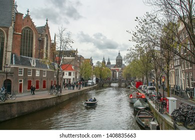 Amsterdam/Holland; 04/30/2016. Canal of Oudezijds Voorburgwal and Basilica of Saint Nicholas at the background, Amsterdam.