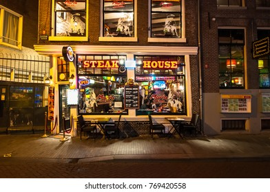 Amsterdam-May 01: Amsterdam local steakhouses and restaurants full of people at night in red-light district on May 01,2015 in Amsterdam, the Netherlands.