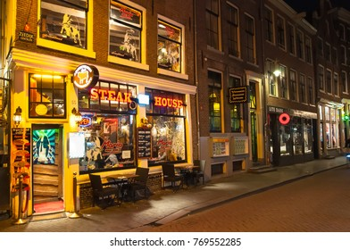 Amsterdam-May 01: Row of local steakhouses and restaurants at night in red-light district full of customers in down town on May 01,2015 in Amsterdam, the Netherlands.