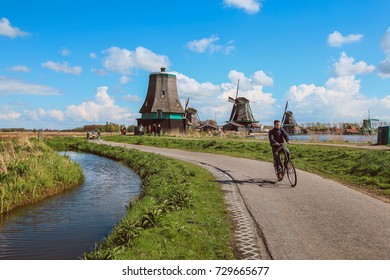 Amsterdam-Netherlands, April 18, 2017 : One man riding bycicle at traditional village with dutch windmills and river at Zaanse Schans, Holland, Netherlands.