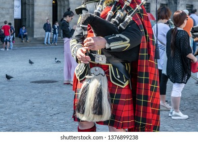 AMSTERDAM/NETHERLANDS - July 19, 2015. Scottish bagpipe player in red kilt plays the bagpipes for tourists in the Dam square in Amsterdam. City performances for tourists in Holland.
