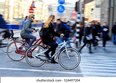 Amsterdam,Netherlands - November 22, 2016 : Panning shot of women on bicycle with people walking in the background on a zebra line in the center of Amsterdam