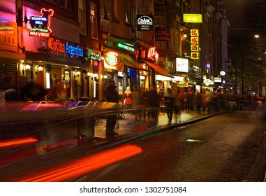 Amsterdam,Netherlands- October 30 2011: Night image of blured people walking on the colorful Dam Street leading to the famous Dam Square in the Centrum borough of Amsterdam city.