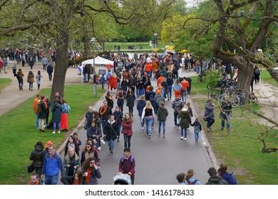 AMSTERDAM,NETHERLANDS-27 APRIL,2019: Big group of people walking in green park Vondelpark near Vincent Van Gogh museum on King's Day celebration in Kingdom of Netherlands