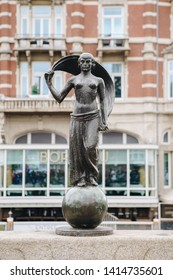 AMSTERDAM,NETHERLANDS-27 APRIL,2019: Statue of Roman Goddess Lady Fortune (dutch: Vrouwe Fortuna) on canal bridge from Rokin to Muntplein,Amsterdam.Built in 1948 by sculptor Hildebrand Lucien Krop