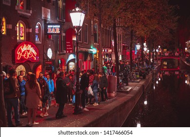 AMSTERDAM,NETHERLANDS-29 APRIL,2019: Crowd of international tourists walking on streets of Red Light District of Amsterdam.Prostitute district - The most popular tourist attraction in Netherlands