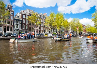 AMSTERDAM,NETHERLANDS-APRIL 27: Amsterdam canal full of boats with people in orange on King's Day on April 27, 2015, the Netherlands. Kings Day is biggest festival on the birth of Dutch royalty.