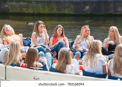 AMSTERDAM,NETHERLANDS-APRIL 27: Local girls celebrate King's Day in a boat on April 27,2015. Amsterdam where an average of 700.000 visitors join locals in the world's largest street party.