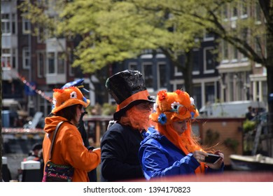AMSTERDAM,NETHERLANDS-APRIL 29. 2019. Crowd of people dressed in orange celebrate King's Day in Amsterdam. King's Day is an open-air festival in Amsterdam, on the king birthday.