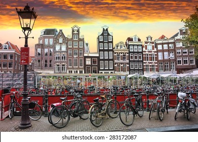 AMSTERDAM,NETHERLANDS,OCTOBER, 06, 2014: Sunset in Amsterdam.Bicycle parking and traditional old dutch buildings.Flower market on Single canal, Netherlands. Amsterdam is the bicycle capital of Europe