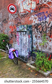 AMSTERDAM,NETHERLANDS,OCTOBER,07:Bicycle street parking near the red brick wall with graffiti.Amsterdam - the bicycle capital and one of the most  original special cities of Europe on October 07,2014