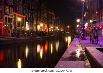 Amsterdam's red light district at night. There are close to 300 display windows with sex workers waiting for their next customer.