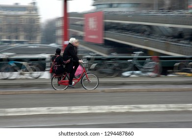 Amsterdam/The Netherlands - January 2012 White haired man riding a bike with a young girl on the back, passing on a bridge in Amsterdam.