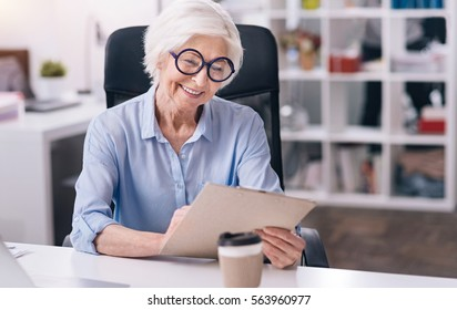 Amused aged woman working in the office