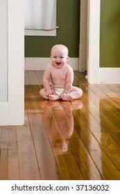 Amused baby sitting on floor wearing diaper