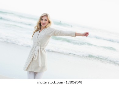 Amused blonde woman in wool cardigan stretching her arms on the beach