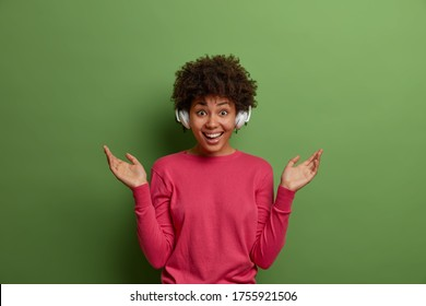 Amused carefree Afro American woman listens music in headphons, keeps hands raised, shows palms, chils and enjoys song, smiles positively, likes new album of favorite singer, poses over green wall