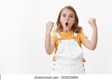 Amused cheerful young blond girl child, celebrating victory, feeling excited like winner, fist pump triumphing, say yes hooray, pouting proudly, stand white background enthusiastic