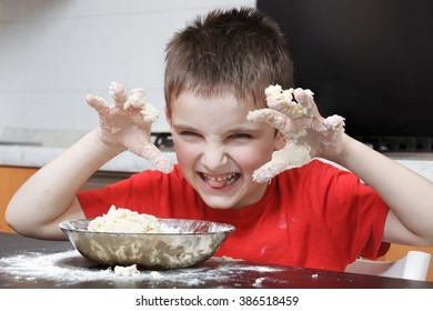 amused child with dough on hands in the kitchen