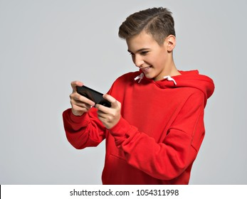Amused teenager playing games on smartphone   - posing at studio