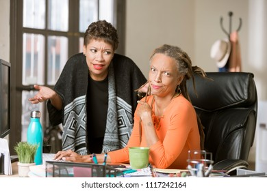 Amused woman points at clueless coworker