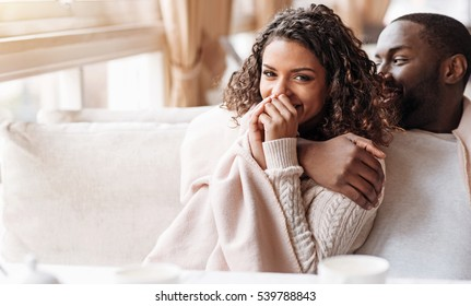 Amused young African American couple sitting and hugging