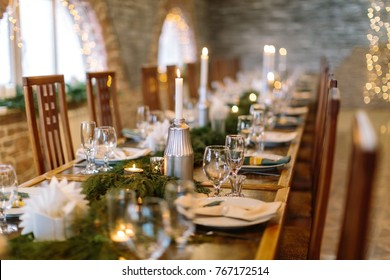amusement, entertainment, illumination concept. on the blured background of served table and twinkle lights there are lots of plates, candles, shining glasses and silverware