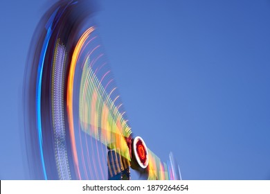 Amusement park blurred effect. Abstract illuminated background Spinning defocused carnival carousel long exposure shooting