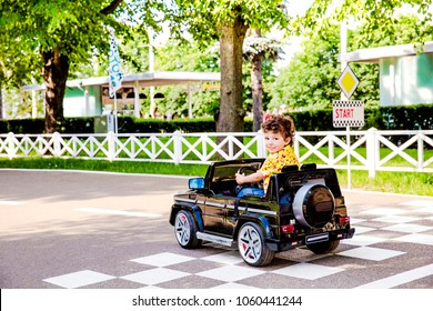 Amusement Park, a funny boy rides on a toy electric car on a sunny summer day, finish marking
