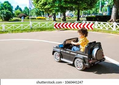 Amusement Park, a funny boy rides on a toy electric car on a sunny summer day