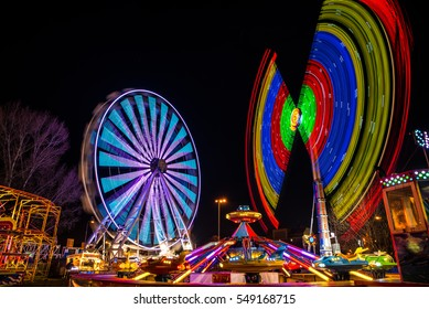 Amusement park at night - ferris wheel and pendulum ride in motion