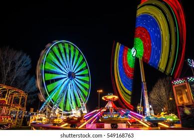 Amusement park at night - ferris wheel and pendulum ride in motion