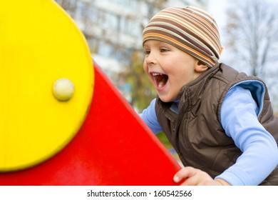 Amusing boy clambering on a children's hill