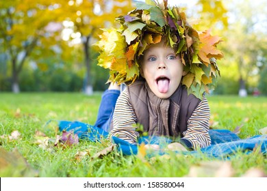 Amusing four-year-old boy in wreath from maple leaves lies on a grass and puts out tongue