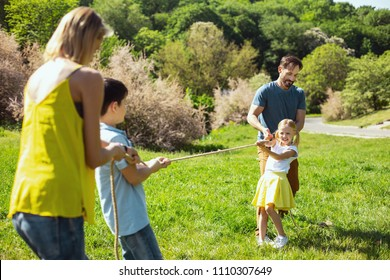 Amusing. Happy loving father helping his daughter while she pulling a rope with her brother