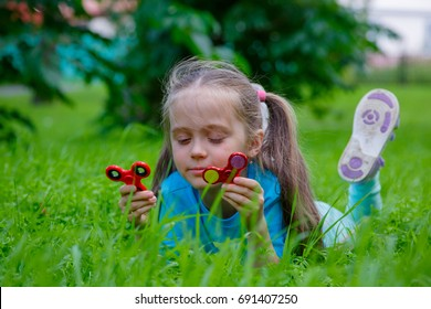 Amusing little girl lie on grass smiling and playing in spinner