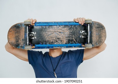 Amusing man holding board with both hands. In front of the head like a mask, blocking it. Board head, silly fun, joke. Indoors in front of a white wall.