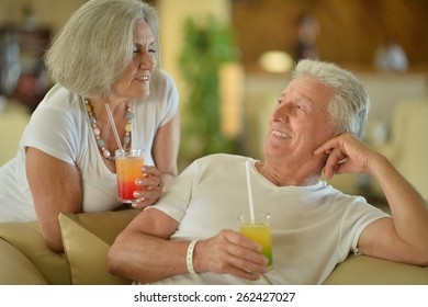 Amusing old couple on vacation drinking cocktail