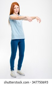 Amusing pretty young woman standing and posing like a zombie isolated over white background