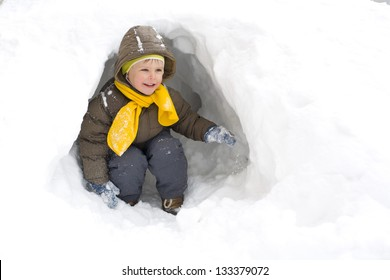 Amusing smiling kid in the winter in a snow cave