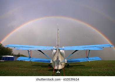 AN-2 airplane on the airfield. Rainbow over the sky
