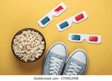 Anaglyph disposable paper 3d glasses with old school style sneakers and popcorn bowl on yellow background. Top view. Retro 80s
