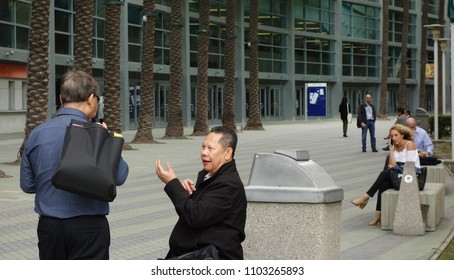 Anaheim, CA / USA - May 30, 2018: Two Asian conference attendees talk animatedly in the palm courtyard of the Anaheim Convention Center